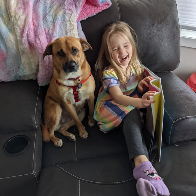 Girl reading a book with her foster dog