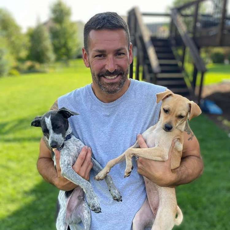 Foster dad holding his two dogs